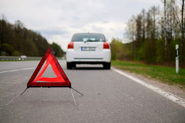 Roadside triangle behind broken car on side of road