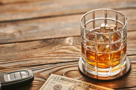 Glass of whiskey or alcohol drink with ice cubes and car key on rustic wooden table with copy-space. Drink and drive and alcoholism concept. Safe and responsible driving concept