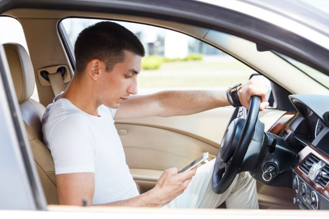 Young man looking at phone texting while driving